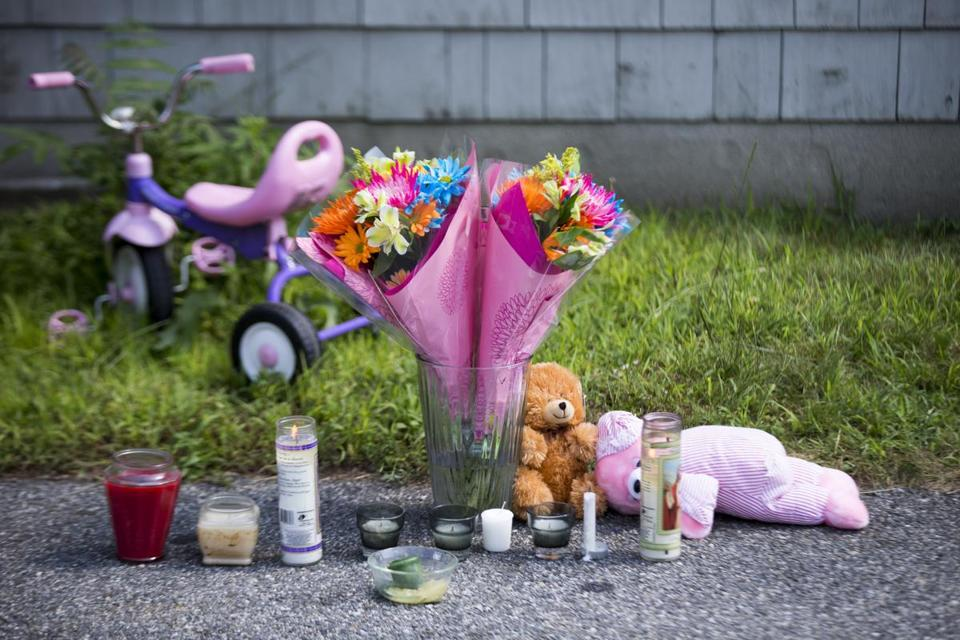 A memorial sat in front of the home where two children, one of whom died, were removed by paramedics in Auburn on Saturday.